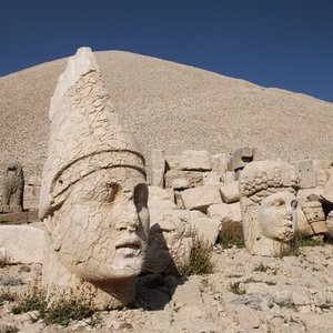 Whose heads lie on the slopes of Mount Nemrut, a major tourist attraction in Turkey?